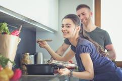 Paar het koken samen in hun keuken thuis Stock Afbeeldingen