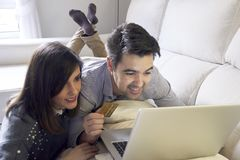 paar het kopen laptop die op de laag thuis liggen stock foto's