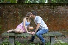 Paar het kussen over cake die één jaarverjaardag vieren stock foto's
