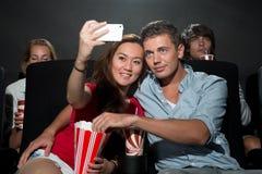 Paar het letten op film bij bioskoop en het fotograferen van Stock Foto's