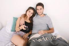 Paar het letten op films in bed Stock Afbeelding