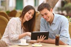 Paar het letten op media in een tablet in een restaurant Stock Afbeeldingen