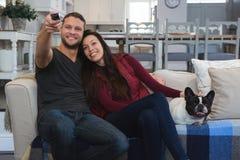 Paar het letten op televisie met hun huisdierenhond in woonkamer royalty-vrije stock fotografie