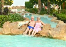 Paar het ontspannen bij pool Stock Afbeelding