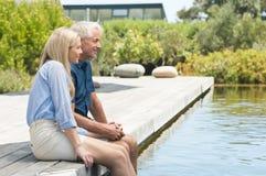 Paar het ontspannen bij poolside stock foto's