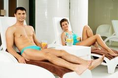 Paar het ontspannen dichtbij zwembad Stock Foto's