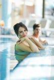 Paar het ontspannen door de kant van de pool Stock Foto