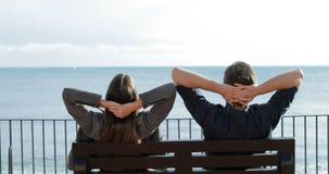 Paar het ontspannen het letten op oceaan in een bank stock video