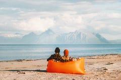 Paar het ontspannen in luchtlanterfanter die op strand van overzees en bergenmening genieten royalty-vrije stock foto