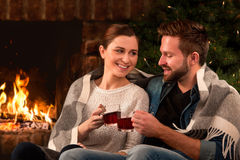 Paar het ontspannen met glas wijn bij open haard Royalty-vrije Stock Foto's