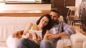 Paar het ontspannen op bank en het gebruiken van digitale tablet stock footage
