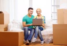 Paar het ontspannen op bank met laptop in nieuw huis stock foto