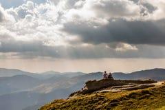 Paar het ontspannen op de bovenkant als de bergen Royalty-vrije Stock Foto's