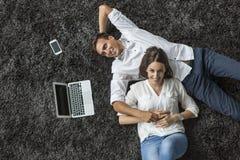 Paar het ontspannen op het tapijt Stock Foto's