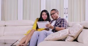 Paar het ontspannen in woonkamer en gebruikstablet stock video