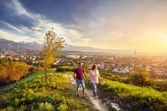 Paar in het park bij de mening van de zonsondergangstad stock fotografie