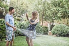 Paar het spelen met een tuinslang en buiten het bespuiten van elkaar in de tuin Stock Fotografie