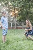 Paar het spelen met een tuinslang en buiten het bespuiten van elkaar in de tuin Stock Foto's