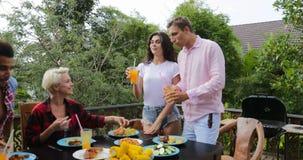 Paar het vertellen toost die mensen opstaan die op terras jonge vrienden eten die bij lijst in openlucht mededeling zitten stock video