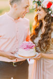 Paar het vieren bij picknick, de jonge die mens en de cake van de vrouwenholding met roze bloemen, close-up wordt verfraaid Stock Foto's