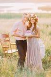 Paar het vieren bij picknick, de jonge die mens en de cake van de vrouwenholding met roze bloemen, houten stoelen op achtergrond  Royalty-vrije Stock Fotografie
