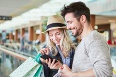Paar het winkelen gebruikssmartphone app stock afbeeldingen