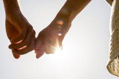 Paar-Hände, die mit Sun-Strahlen zusammenhalten Lizenzfreie Stockfotografie