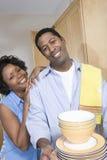 Paar-Holding-Stapel von gewaschenen Platten und von Schüssel Stockbilder