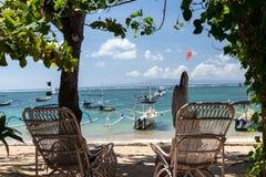 Paar houten stoel dichtbij het strand, het tropische eiland van Bali, Indonesië royalty-vrije stock afbeelding