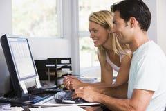 Paar in huisbureau dat computer en het glimlachen gebruikt Stock Foto