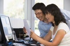 Paar in huisbureau met computer en administratie Stock Afbeeldingen