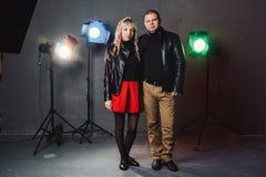 Paar im Schwarzen kleidet während des Bildschießens im Studio und in den Scheinwerfern an Lizenzfreies Stockbild