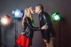 Paar im Schwarzen kleidet während des Bildschießens im Studio und in den Scheinwerfern an Lizenzfreie Stockfotos
