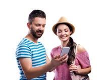Paar im Sommer kleidet mit dem Smartphone und nimmt selfie Lizenzfreie Stockfotos