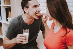 Paar ist, trinkend essend und auf Couch lizenzfreie stockfotos