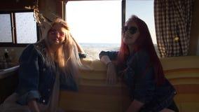 Paar jonge vrouwen op een bank op de achtergrond van het overzees op de wegvrachtschepen stock videobeelden