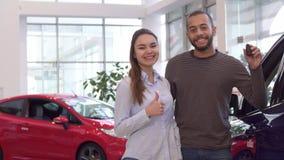 Paar kauft Auto an der Verkaufsstelle lizenzfreies stockbild