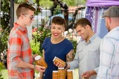 Paar kauft Honig am Landwirt-Markt Stockfotografie
