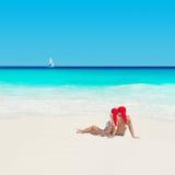 Paar in Kerstmishoeden bij oceaanstrand met jacht, nieuwe jaren va Stock Foto