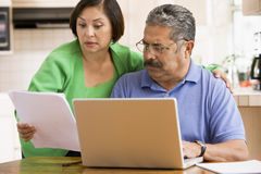 Paar in keuken met laptop en administratie stock fotografie