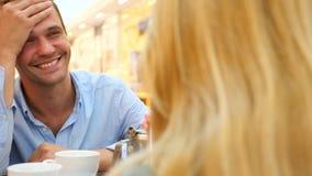 Paar in Koffie De man en de mooie vrouw op een datum lachen slow-motion 4k, close-up De ruimte van het exemplaar stock videobeelden