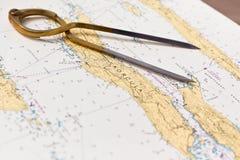 Paar kompassen voor navigatie op een overzeese kaart Stock Afbeeldingen