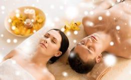 Paar in kuuroordsalon die op de massagebureaus liggen stock afbeeldingen
