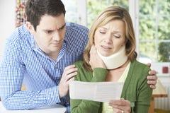 Paar-Lesebuchstabe in Bezug auf die Nackenverletzung der Frau lizenzfreies stockfoto