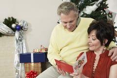 Paar-Lesegruß-Karte mit Weihnachtsgeschenken außerdem Lizenzfreie Stockfotos