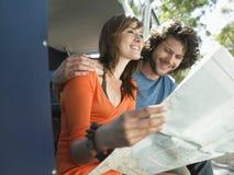 Paar-Lesekarte während der Autoreise Lizenzfreies Stockfoto