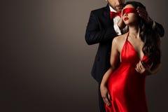 Paar-Liebes-Kuss, Mann und sexy Frau mit verbundenen Augen im roten Kleid Stockfoto