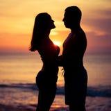 Paar in liefde achter licht silhouet op overzees Stock Afbeelding