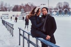 Paar in liefde, datum bij de ijsbaan, een meisjeszitting op een vangrail en het omhelzen met haar vriend royalty-vrije stock foto