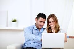 Paar in liefde die een computer thuis met behulp van Stock Fotografie